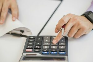 man creating budget with calculator