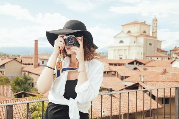 13th Month Pay Investments - woman tourist taking a photo